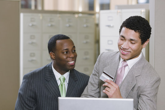 Multi-ethnic businessmen with laptop holding credit card