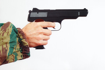 Hand in camouflage uniform with army pistol