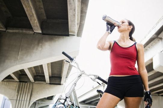 Hispanic woman with bicycle drinking water