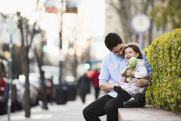 Hispanic father and daughter laughing on city street