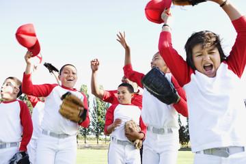 Multi-ethnic boys in baseball uniforms celebrating