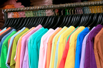 Shop shirts colorful fabric hanging on a rack.