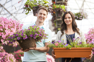 Caucasian couple carrying potted flowers in plant nursery