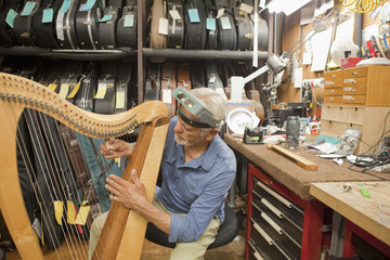Hispanic craftsman working on harp in shop