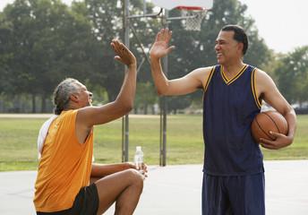 African men high-fiving on basketball court