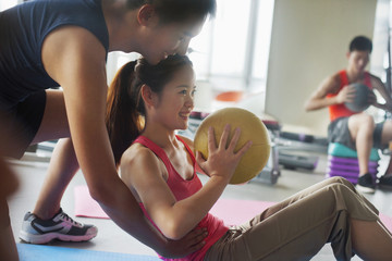 Chinese woman working with trainer in gym