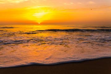 Golden sunrise sunset over the sea ocean waves