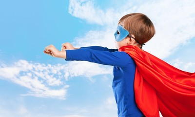 Kid. Superhero kid against blue sky background. Girl power