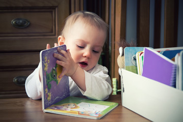 one-year-old baby girl  browses book with interest.