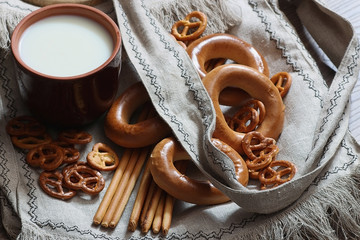 food milk in a glass straw bagels and pretzels on flax