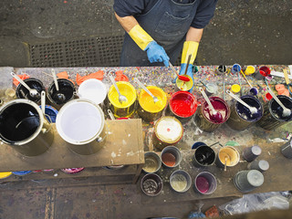 Hispanic worker mixing paint in workshop