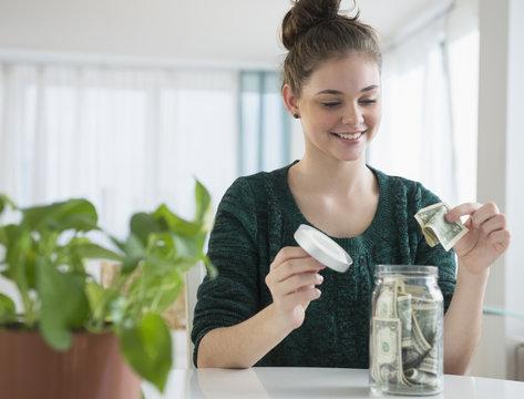 Hispanic girl putting money in savings jar