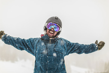 Caucasian snowboarder cheering in snow