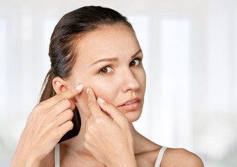 Woman. Young woman squeezing pimple on her cheek on white