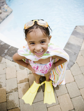 Hispanic girl standing at poolside in flippers