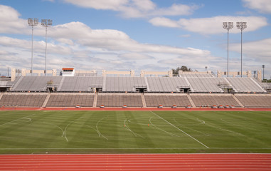College Level Track Stadium Puffy Clouds Blue Sky
