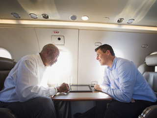 Businessmen talking on airplane