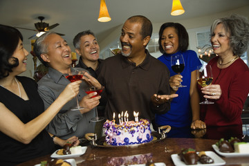 African man celebrating birthday with multi-ethnic friends