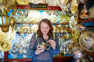 Tourist selecting teapot on Moroccan market