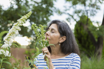 Hispanic woman smelling flowers in garden