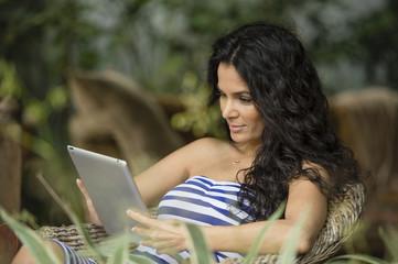 Hispanic woman using tablet computer