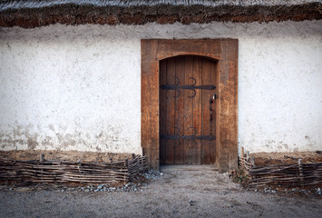 Wooden old door with lock and clay wall. Background