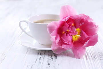 Pink tulip with cup of coffee on wooden background