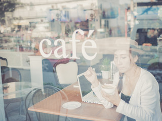 Asian woman drinking coffee and using computer in cafe. Photo fi