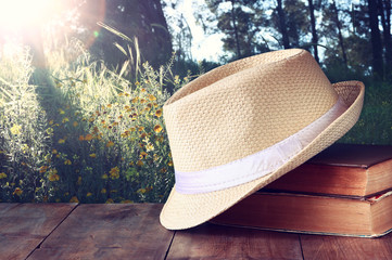fedora hat and stack of books over wooden table and evening natu