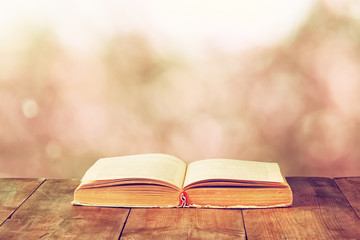 open book over wooden rustic table in front of blurred bokeh lig