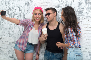 two women and man friends taking selfie together wearing summer