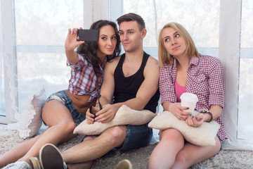 two girls and guy friends taking selfie together wearing summer