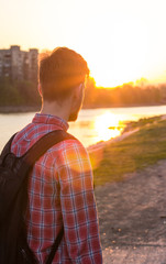 young man on a background of city sunset