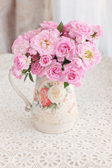 Beautiful fresh pink roses on a table. light background.