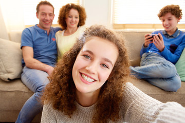 Happy young girl taking selfie with parents in the background