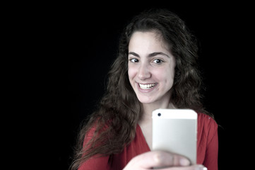 Young female holding a smartphone taking selfie