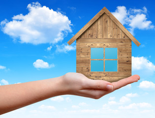 Wooden house in hand on the background blue sky