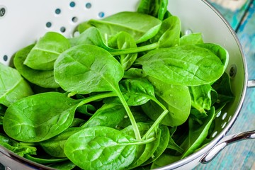 raw fresh spinach in a white colander closeup