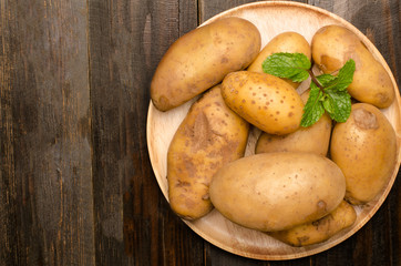 Potatoes on wooden plate