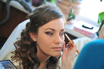 Woman applying make up for bride in her wedding day near mirror