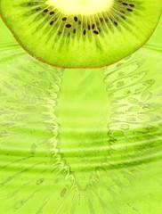 Half of ripe green kiwi slice on green abstract background.