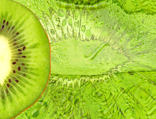Green kiwi slice on green abstract background.