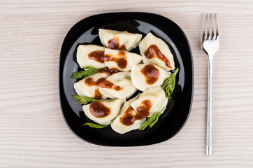 Boiled dumplings in plate and fork on table, top view