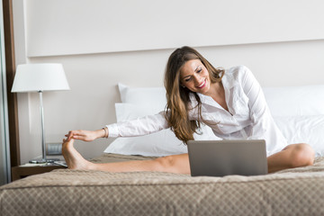 Beautiful woman using a notebook in bed and stretching