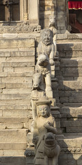 Statues on the steps of an ancient temple in Bhaktapur, Nepal