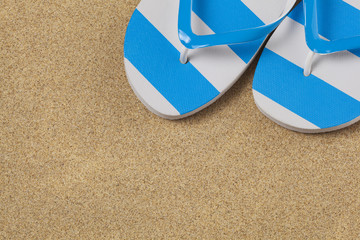 Blue flip flop shoes and on a yellow sand beach