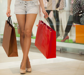 Legs of shopaholic wearing jeans shorts while carrying several p