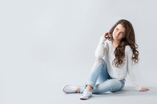 Cute woman sitting on the floor and smiling