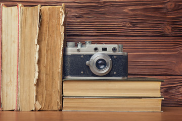 Retro Camera and Stack of Books Over Wooden Background