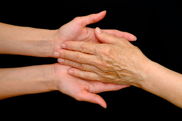Old woman and young woman holding hands together